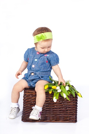 A small child sitting on a basket next to a bouquet of flowers photo