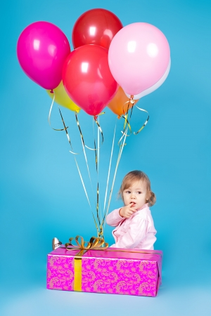 Beautiful little girl with balloons and a gift celebrating a birthday  Studio shot on a blue background  photo