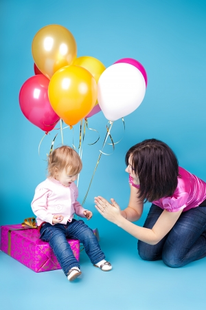 The family, mother and child celebrate with a gift and balloons photo