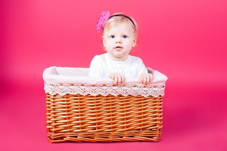 A small child playing in a basket  Studio shooting  photo