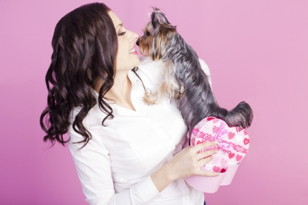 Young brunette with a dog was presented with a box of chocolates Stock Photo - 16501964