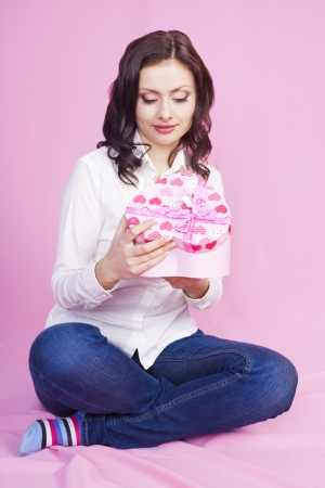Young brunette was presented with a gift on a pink background photo