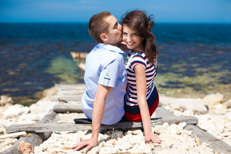 Couple in love, young guy and a beautiful brunette girl posing in the beach, enjoying their summer holiday together Stock Photo - 16549009