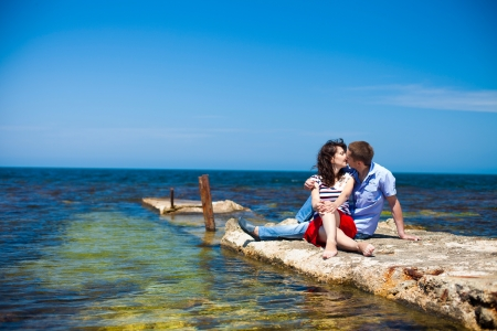 Couple in love, young guy and a beautiful brunette girl posing in the beach, enjoying their summer holiday together  photo