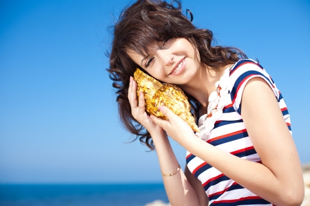 Beautiful brunette listens seashell on the beach photo