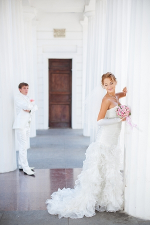 Young couple in love bride and groom posing near the white columns, standing at a distance from each other in their wedding day in summer Stock Photo - 16536982