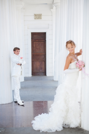 Young couple in love bride and groom posing near the white columns, standing at a distance from each other in their wedding day in summer  Stock Photo - 16536968