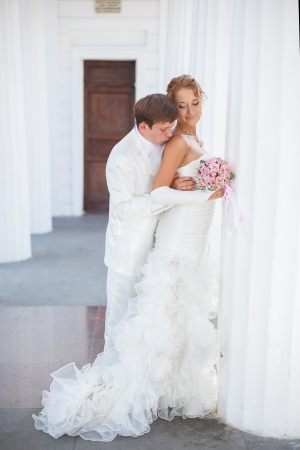 Young couple in love bride and groom posing near the white columns in their wedding day in the summer Stock Photo - 16536971