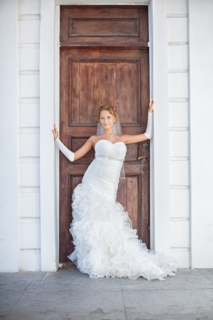 bilding: Young beautiful bride posing in front of old wooden door of the white building in the city  Stock Photo