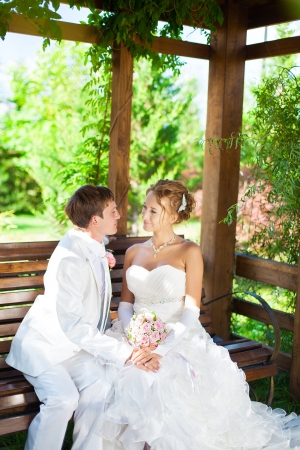 Couple in love bride and groom posing sitting on a wooden bench in a gazebo in their wedding day in summer  photo