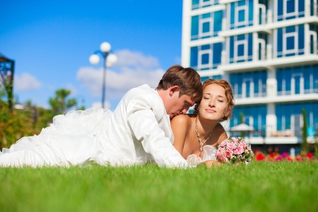 Young couple groom and bride in a beautiful white dress with a bouquet posing in a park lying on the green grass Stock Photo - 16622670