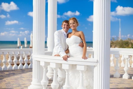 Young couple in love bride and groom posing on the beach in the area with white columns on the background of bright blue sky  Wedding day in the summer  Series  Stock Photo