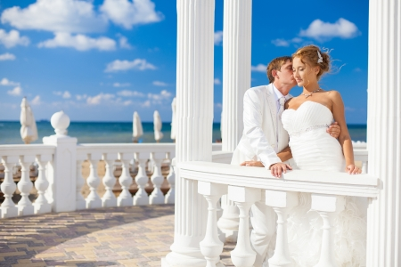 woman beach dress: Young couple in love bride and groom posing on the beach in the area with white columns on the background of bright blue sky  Wedding day in the summer  Series  Stock Photo