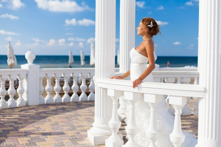 belongs: Beautiful bride posing on the beach in white columns on a background of blue sky in her wedding day in summer