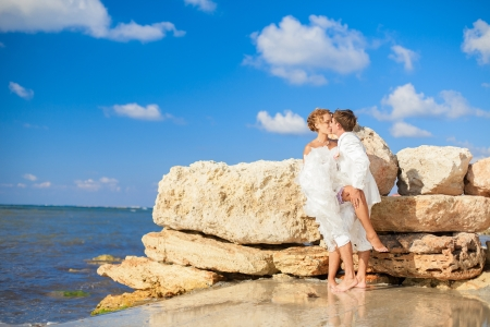 Couple in love young bride and groom hugging on the shore of the blue sea in a luxurious white dress posing next to a wall of yellow stones from the sea floor  Wedding day in the summer  Series