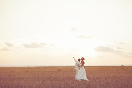 Young couple in love bride and groom posing in a field with yellow grass on sunset background in their wedding day in the summer  Series