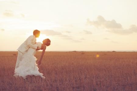 femme romantique: Jeune couple dans l'amour mari�e et le mari� posant dans un champ d'herbe jaune sur fond coucher de soleil dans leur journ�e de mariage dans la s�rie d'�t�