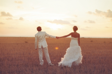 Young couple in love bride and groom posing in a field with yellow grass on sunset background in their wedding day in the summer  Series  photo