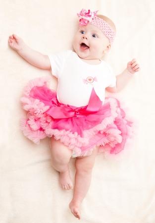 armband: Bambino felice in un tut� rosa e una benda sulla testa con un fiore Archivio Fotografico