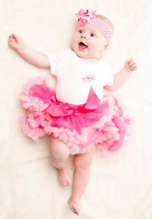 Happy child in a pink tutu and a bandage on his head with a flower Stock Photo