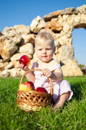 The child, a basket of apples Stock Photo - 16583109