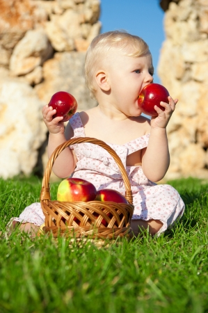 The child, a basket of apples Stock Photo - 16583107