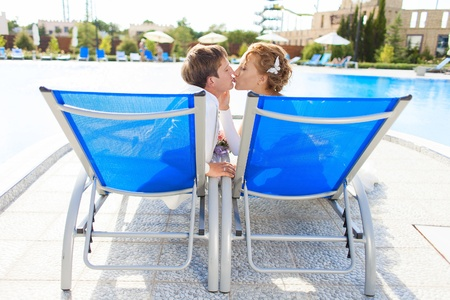 Beautiful young couple bride and groom posing on deck chair on a background a swimming pool in their wedding day in summer  photo