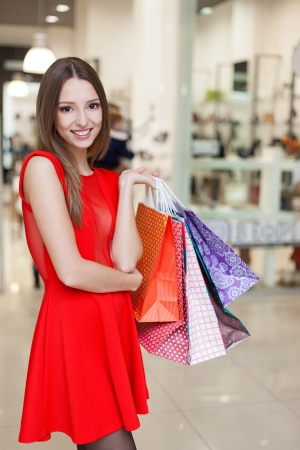 Beautiful young woman in a luxurious red dress posing with shopping bags in mall on the background of shop windows. Series. photo