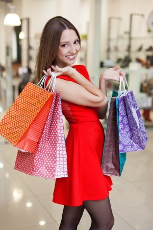 Beautiful young woman in a luxurious red dress posing with shopping bags in mall on the background of shop windows. Series.