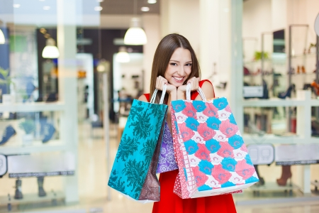 Schöne junge Frau in einem luxuriösen roten Kleid posiert mit Einkaufstaschen in mall auf dem Hintergrund von Schaufenstern. Serie. Standard-Bild - 16637345