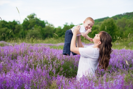 Mother with a cute baby posing sitting on a field of purple flowers around Stock Photo - 16715530