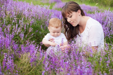 Mother with a cute baby posing sitting on a field of purple flowers around  Stock Photo - 16715539