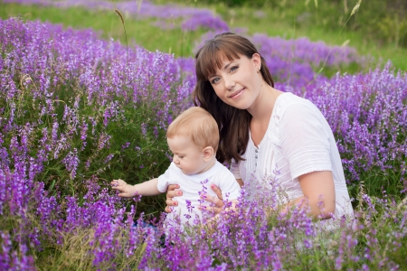 Mother with a cute baby posing sitting on a field of purple flowers around Stock Photo - 16715534