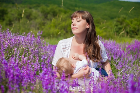 Mother breastfeeding her baby in a field of purple flowers