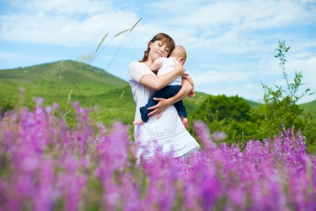 Beautiful young mother posing with a small child in her arms while standing in a field of purple flowers on the background of mountain and blue sky  Series Stock Photo - 16715527