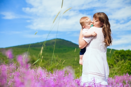 Beautiful young mother posing with a small child in her arms while standing in a field of purple flowers on the background of mountain and blue sky  Series  photo