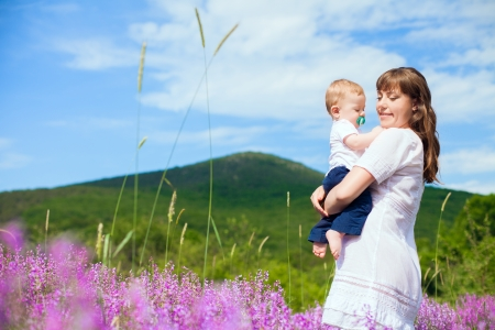 Beautiful young mother posing with a small child in her arms while standing in a field of purple flowers on the background of mountain and blue sky  Series  Stock Photo - 16715524