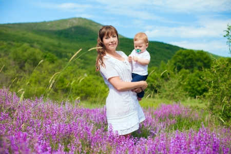 Beautiful young mother posing with a small child in her arms while standing in a field of purple flowers on the background of mountain and blue sky  Series  Stock Photo - 16715535