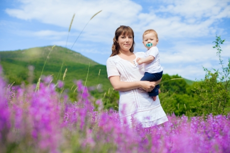 Beautiful young mother posing with a small child in her arms while standing in a field of purple flowers on the background of mountain and blue sky  Series  Stock Photo - 16715523