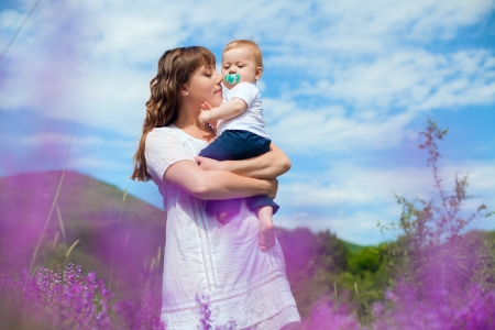 Beautiful young mother posing with a small child in her arms while standing in a field of purple flowers on the background of mountain and blue sky  Series Stock Photo - 16715526