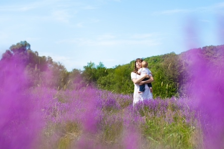 Beautiful young mother posing with a small child in her arms while standing in a field of purple flowers on the background of mountain and blue sky  Series Stock Photo - 16715520