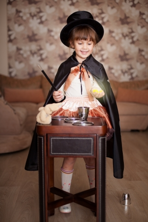 Cute child posing in Attire conjurer with a magic wand at the table with magical accessories at home  Series  photo