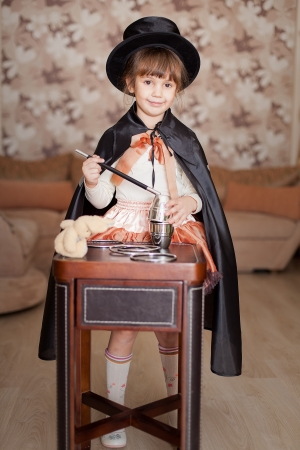 bewitchment: Cute child posing in Attire conjurer with a magic wand at the table with magical accessories at home  Series  Stock Photo