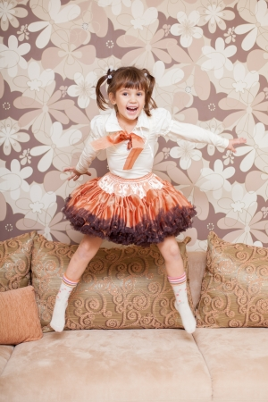 baby 4 5 years: Beautiful little girl jumping on the couch at home Stock Photo