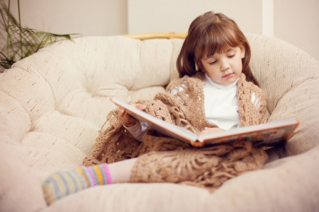 beauty child in shawl reading a book while lying on the couch Stock Photo - 16715504