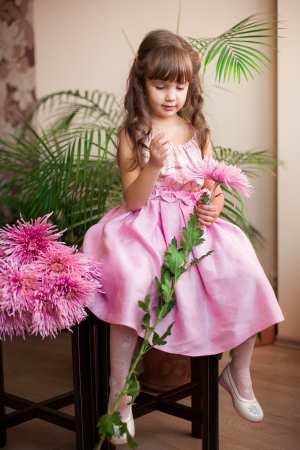 Beautiful little girl posing with a large bouquet of flowers in a luxuus pink dress at home  Stock Photo - 16710940