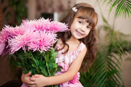 little girl posing: Beautiful little girl posing with a large bouquet of flowers in a luxurious pink dress at home  Stock Photo