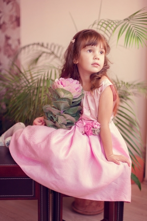 Beautiful little girl model view in a luxury pink dress and flower posing at home on the table  Stock Photo - 16710939