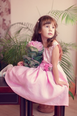 Beautiful little girl model view in a luxury pink dress and flower posing at home on the table  Stock Photo - 16710941