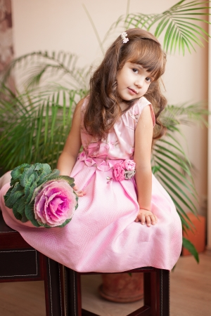 Beautiful little girl model view in a luxury pink dress and flower posing at home on the table  photo